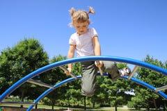 A menina de quatro anos que joga no campo de jogos. Fotografia de Stock
