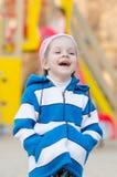 Menina de quatro anos que ri no campo de jogos Fotografia de Stock Royalty Free