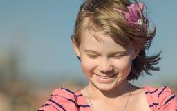 A menina de riso é um adolescente no fundo do céu azul Imagens de Stock