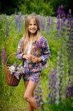 A menina de riso bonita em um campo do lupine roxo floresce fotografia de stock royalty free