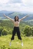 A menina de riso bonito está saltando contra o contexto das montanhas foto de stock royalty free