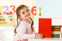 Menina de riso com livros Fotografia de Stock Royalty Free