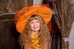menina de riso da bruxa do Dia das Bruxas no chapéu com vassoura Fotografia de Stock Royalty Free