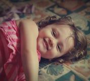 Menina de riso da criança que encontra-se na cama. Fotografia de Stock