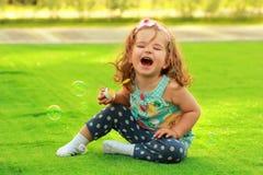 Menina de riso do bebê de um ano que aprende fundir bolhas de sabão e que senta-se no gramado ensolarado foto de stock