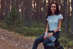 A menina de riso do moderno do turista guarda uma garrafa da água, parada para descansar na floresta bonita do outono foto de stock