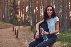 A menina de riso do moderno do turista guarda uma garrafa da água, parada para descansar na floresta bonita do outono imagens de stock