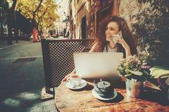 A menina de riso está falando no telefone no café Imagens de Stock Royalty Free