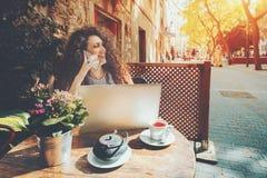 A menina de riso está falando no telefone no café Foto de Stock