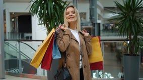 A menina de riso guarda sacos de compras em seus ombros que estão na alameda vídeos de arquivo