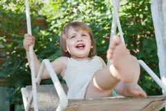 Menina de riso no balanço no verão Imagem de Stock