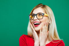 Menina de riso nos monóculos e na parte superior vermelha no fundo verde Retrato do close up do louro novo com cabelo longo e Imagens de Stock Royalty Free