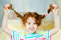 A menina de riso puxa para cima sua trança à mão e mostra-lhe teeths C Fotos de Stock