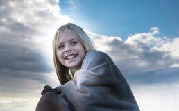 Menina de riso que senta nas rochas a praia envolvida em uma toalha Fotografia de Stock