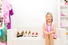 A menina de riso senta-se no sofá que escolhe sapatas Fotografia de Stock Royalty Free