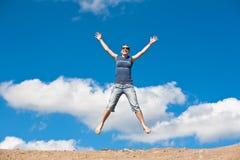 Menina de salto com mãos acima de encontro Fotos de Stock