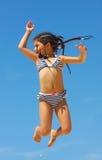Menina de salto de encontro ao céu azul Imagens de Stock