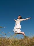 Menina de salto feliz no campo Foto de Stock Royalty Free