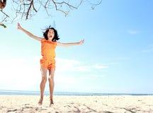 Menina de salto na praia fotos de stock royalty free