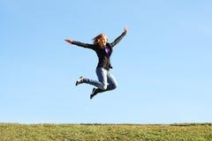 Menina de salto no campo no verão. Liberdade imagem de stock