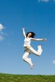 Menina de salto no prado Fotos de Stock Royalty Free