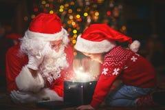 Menina de Santa Claus e da criança com o presente mágico brilhante no Natal fotografia de stock royalty free