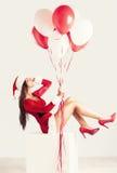 Menina de Santa no vestido curto do xmas do vermelho e no chapéu de Papai Noel com balões fotografia de stock