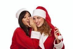 Menina de Santa que sussurra a sua orelha da amiga fotografia de stock