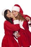 Menina de Santa que sussurra a sua orelha da amiga fotografia de stock royalty free