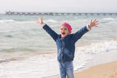 A menina de sete anos exulta a chegada do mar na costa na primavera imagens de stock royalty free