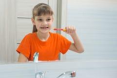 A menina de sete anos olha si mesma no espelho antes de escovar seus dentes imagens de stock royalty free