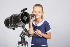 Menina de sete anos que está ao lado do telescópio e dos olhares do refletor misteriosamente no céu Imagem de Stock