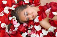 Menina de sono na pétala cor-de-rosa fotografia de stock royalty free