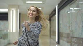 A menina de sorriso à moda corre para uma venda no shopping filme