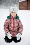 A menina de sorriso adorável da criança tem o divertimento na neve fotos de stock royalty free