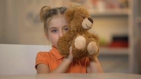 Menina de sorriso adorável que guarda o urso de peluche marrom, criança alegre, infância feliz filme