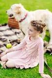 menina de sorriso adorável que olha ausente ao descansar com cão foto de stock royalty free
