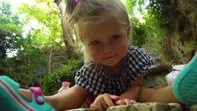 Menina de sorriso adorável que senta-se na rocha na floresta vídeos de arquivo