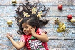 Menina de sorriso alegre bonito com cabelo decorado do Natal com homens de pão-de-espécie fotos de stock