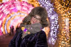 Menina de sorriso alegre alegre do retrato em um tampão da pele do inverno na perspectiva da iluminação da noite no inverno em Mo imagens de stock royalty free