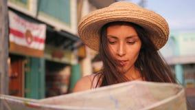 Menina de sorriso atrativa que olha o mapa da cidade e que admira construções velhas da cidade Mulher nova do turista da raça mis filme