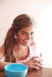 A menina de sorriso bebe o leite Fotografia de Stock