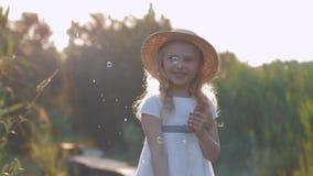 Menina de sorriso bonita alegre em bolhas e em risos dos sopros do chapéu de palha na luz ensolarada vídeos de arquivo