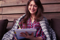 Menina de sorriso bonita coberta com uma cobertura que guarda um whil do jotter imagens de stock