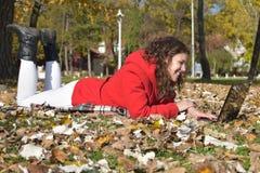 A menina de sorriso bonita com laptop aprecia o outono no parque Fotografia de Stock Royalty Free
