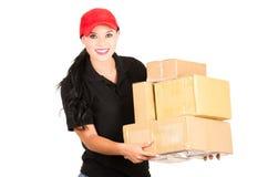 Menina de sorriso bonita da entrega que guarda pacotes Fotografia de Stock