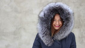 Menina de sorriso bonita do close up que veste o revestimento azul com a capa no inverno, neve da pele filme
