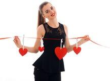 Menina de sorriso bonita em um vestido preto e em guardar uma fita com corações Fotografia de Stock Royalty Free