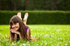 A menina de sorriso bonita está colocando na grama verde fotos de stock royalty free