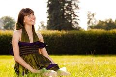 A menina de sorriso bonita está sentando-se na grama Imagem de Stock